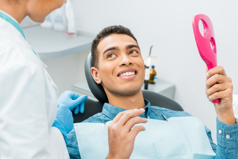 young man smiling sitting in dentist chair after dental visit