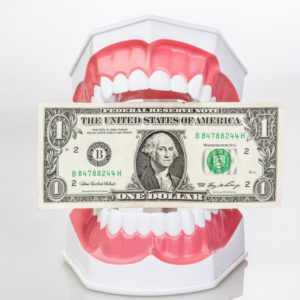 Teeth sitting on a table holding a $1 bill