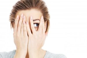 Woman with her hands on her face, peeking between two fingers