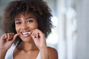 flossing woman smiling because she knows why flossing is important